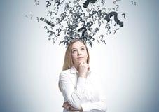 Träumerische blonde Geschäftsfrau, viele Fragen Lizenzfreie Stockfotografie