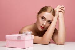 Träumerische Dame mit Geschenkbox Stockfoto