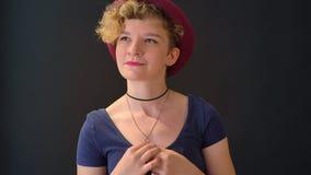 Träumerische hübsche Frau mit dem gelockten blonden Haar im roten Hut lächelnd und lokalisiert auf schwarzem Hintergrund stehend stock video