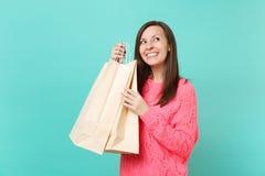 Träumerische junge Frau in der gestrickten rosa Strickjacke, die oben, Pakettaschen mit Käufen nach dem Einkauf halten schaut, de lizenzfreies stockfoto