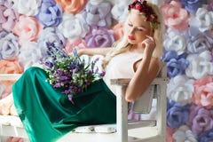 Träumerische junge Frau im Blumendiadem, das auf der weißen Bank w sitzt Lizenzfreies Stockfoto