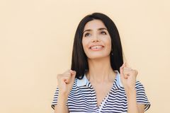 Träumerische positive Frau mit dem schwarzen geraden Haar, hält Hände in den Fäusten, schaut glücklich aufwärts, glaubt an etwas, stockbild
