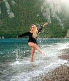Träumerische sinnliche Frau genießt Beschaffenheit von Meer im Wasser spritzt Lizenzfreie Stockfotografie