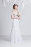 Träumerische und schöne junge Braut in einem luxuriösen Spitzehochzeitskleid Lizenzfreie Stockbilder