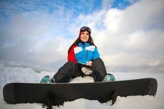 Träumerischer Frauensnowboarder sitzt auf Berg auf blauem Himmel Stockbild