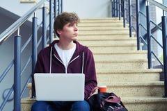 Träumerischer Junge, der im Laptop beim Fenster heraus schauen arbeitet Lizenzfreie Stockbilder