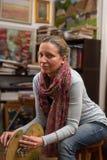 Träumerischer weiblicher Künstler, der in einer Galerie sitzt Stockbild