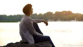 Träumerisches jugendlich Sitzen auf Flussbank und Denken an Richtung des Lebens, Rückseitenansicht lizenzfreie stockfotos