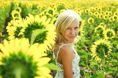 Träumerisches junges Mädchen auf dem Gebiet der Sonnenblumen Lizenzfreies Stockfoto
