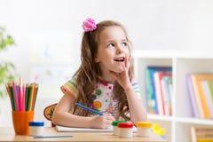 Träumerisches Kindermädchen mit Bleistiften Stockfotos