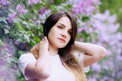 Träumerisches Mädchen nahe dem Fliederbusch lizenzfreie stockfotografie