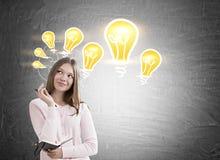 Träumerisches Mädchen und Glühlampen auf Tafel Lizenzfreie Stockfotografie