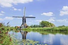 Träväderkvarn som avspeglas i en kanal på en sommardag med en blå himmel och moln, Nederländerna arkivbilder