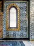 Trävälvt fönster som inramas av guld- blom- modellprydnader över väggen för keramiska tegelplattor med blom- blåa modeller Fotografering för Bildbyråer