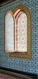 Trävälvt fönster som inramas av guld- blom- modellprydnader Royaltyfria Bilder