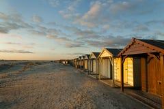 trävästra wittering för strandkojasolnedgång Royaltyfria Bilder