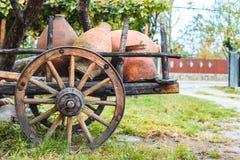 Trävagn som laddas med lerakrukor för vin i en grön trädgård royaltyfri bild