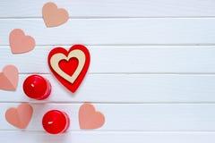 Trävit bakgrund med röda hjärtor och stearinljus Begreppet av Valentine Day Top beskådar arkivfoton