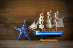 Trävit segelbåt för gammal tappning på trätabellen tappning filtrerad bild nautiskt livsstilbegrepp arkivbild