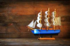 Trävit segelbåt för gammal tappning på trätabellen tappning filtrerad bild nautiskt livsstilbegrepp royaltyfria bilder