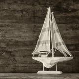 Trävit segelbåt för gammal tappning på trätabellen tappning filtrerad bild nautiskt livsstilbegrepp royaltyfri foto