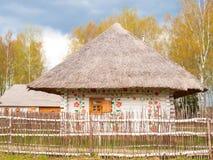 Trävitt pepparkakahus med staketet i rysk by Arkivfoto