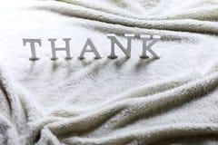 Träwthitebokstaven tackar dig på den skrynkliga mattan Arkivbilder
