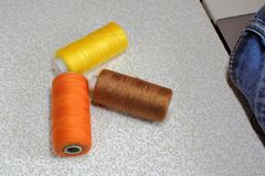 Tråd av varma färger, jeans, symaskin Fotografering för Bildbyråer