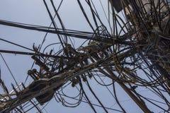 Trådar som fästas till den elektriska polen, kaoset av kablar och wir royaltyfria foton