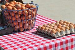 Trådkorg och låda med bruna ägg som är till salu på en bondes marknad Royaltyfri Fotografi