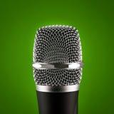Trådlös mikrofon på grön bakgrund Arkivfoton