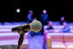 Trådlös mikrofon på ställningen suddighet bakgrund Folk i åhörarna Show på etapp i teatern eller konserthallen royaltyfri fotografi