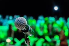 Trådlös mikrofon på ställningen suddighet bakgrund Folk i åhörarna Show på etapp i teatern eller konserthallen royaltyfri bild
