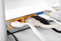 Trådlös router för internet med pluggade kablar Arkivbild
