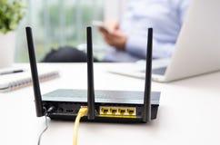Trådlös router och man som använder en smart telefon i hem Arkivfoton