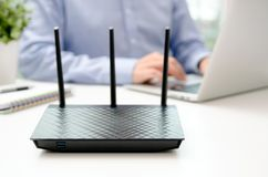 Trådlös router och man som i regeringsställning använder en bärbar dator Royaltyfri Fotografi
