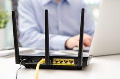 Trådlös router och man som i regeringsställning använder en bärbar dator Fotografering för Bildbyråer