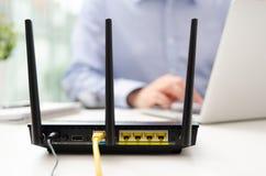 Trådlös router och man som i regeringsställning använder en bärbar dator Royaltyfria Bilder