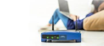 Trådlös router och ungar som använder en bärbar dator i hem routerradio Arkivfoto