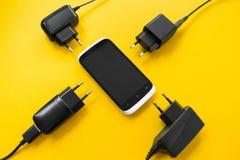 Trådlös uppladdning för smartphonen på en gul bakgrund, begrepp royaltyfria foton