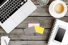 Trådlösa digitala apparater, kaffekopp och tomma kort på arbetsplats Arkivbild