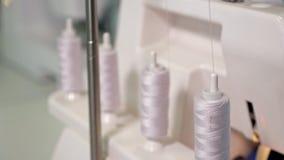 Trådrullning från den stora spolen till den lilla spolen som förbereder sig att sy i symaskin stock video