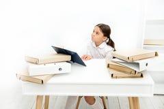 tråkig kurs Borra uppgiftsläxa Bli av med att borra uppgift Sitter den uttråkade eleven för flickan på skrivbordet med mappar och royaltyfria foton