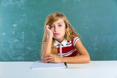 Tråkig ledsen uttrycksstudentskolflicka på skrivbordet Fotografering för Bildbyråer