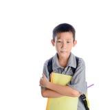 Tråkig skolpojke med den isolerade ryggsäcken och boken arkivbild