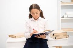 Tråkig uppgift att skriva Hur gör utbildning mer intressant för första gamlor, Boken för flickabarnhållen gör anmärkningen Ungesk royaltyfria bilder