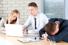 tråkigt arbete Ungt affärsfolk som ser borrat, medan sitta tillsammans på tabellen och se bort Royaltyfri Foto