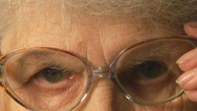 Très dame âgée met dessus des verres et regarder l'appareil-photo clips vidéos