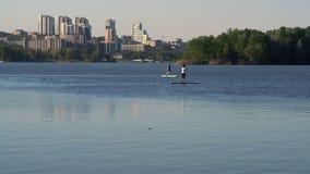 Très possibilité éloignée, fille et Guy Learn à nager sur les petites gorgées sur la rivière sur le fond du ` s de ville banque de vidéos