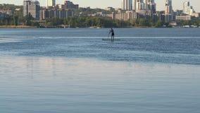 Très possibilité éloignée, jeune Guy Standing Sip sur la petite gorgée sur la rivière sur le fond du ` s de ville banque de vidéos